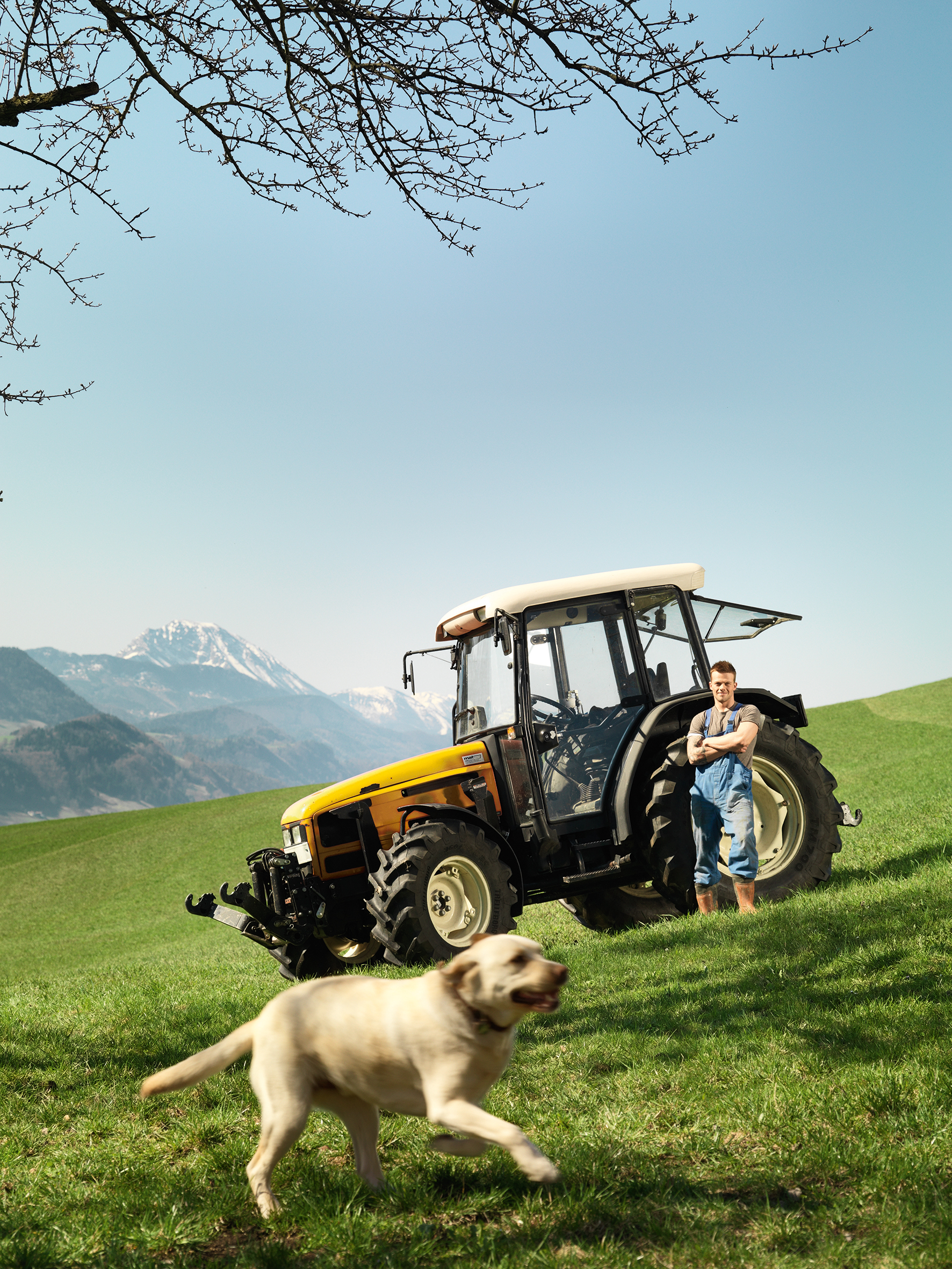 Farmer in front of a yellow tractor