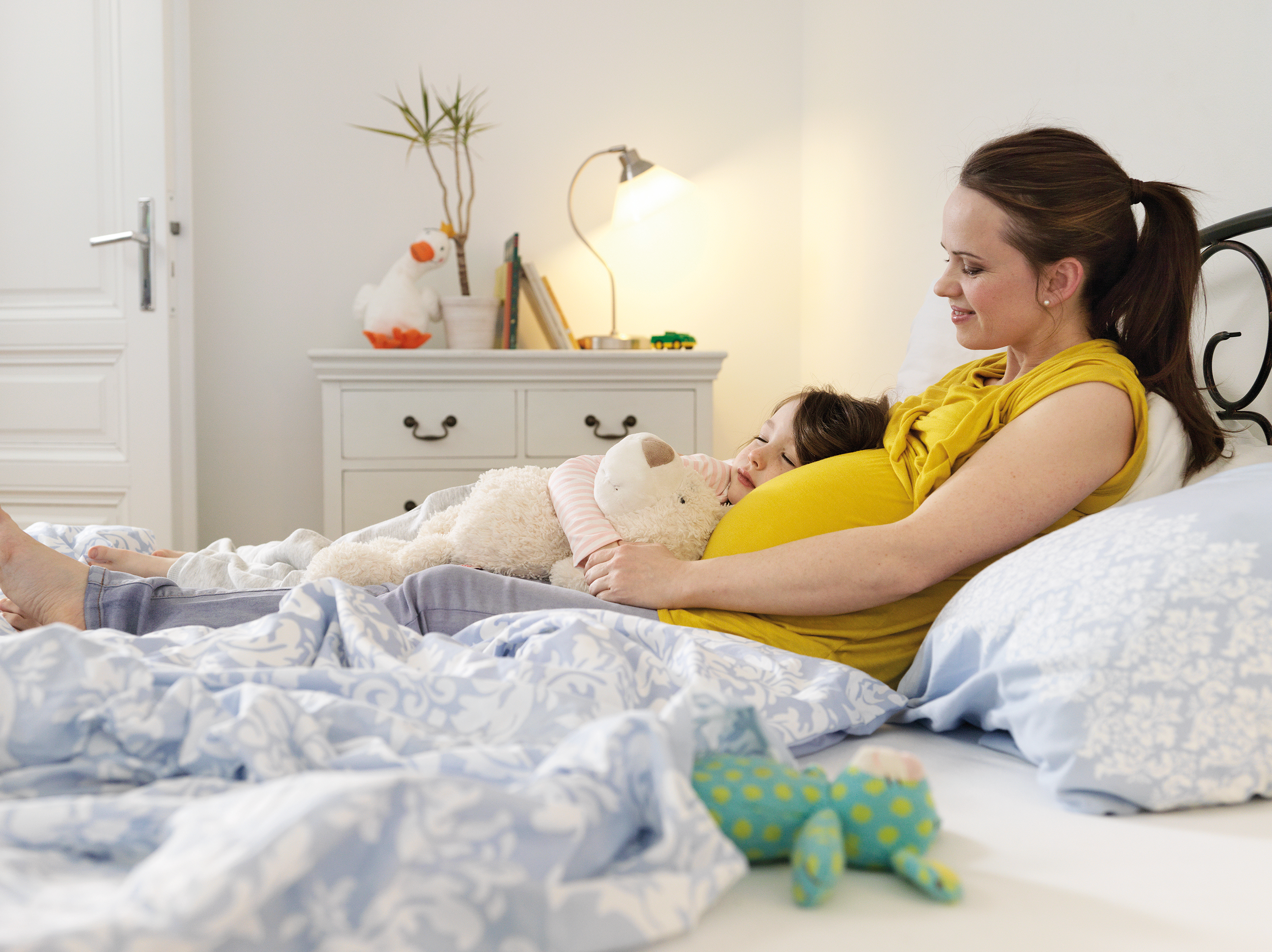 Pregnant woman with child in bed