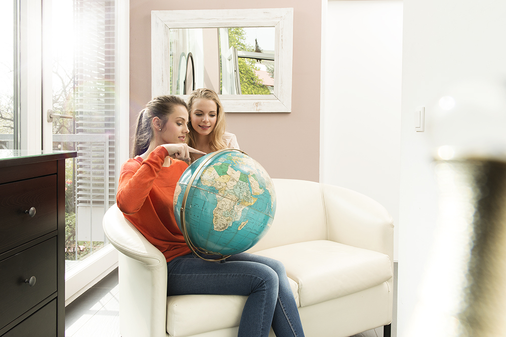 Two girls looking and pointing at a globe