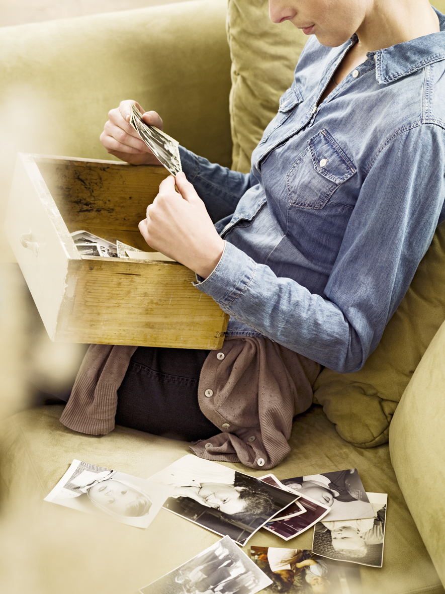Woman looking at old historic pictures sitting on a sofa